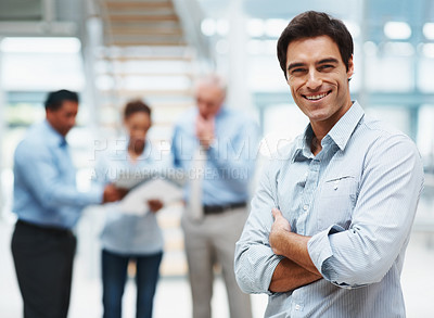 Buy stock photo Happy and handsome businessman with his team mates discussing in the background