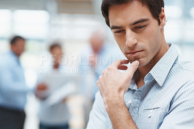 Buy stock photo Closeup of a thoughtful smart business executive with colleagues in the background