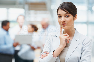 Buy stock photo Portrait of a pretty business woman with team mates working in the background
