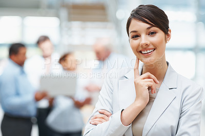 Buy stock photo Beautiful young business executive with colleagues discussing in the background
