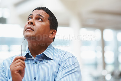 Buy stock photo Mixed race business man looking up in thought with copyspace against blur background