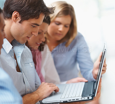 Buy stock photo Group of business colleagues working together on a laptop
