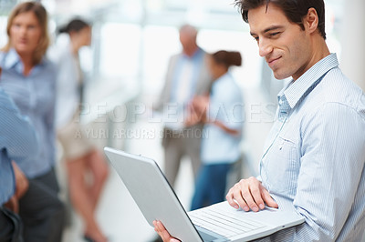 Buy stock photo Portrait of successful business executive using laptop with colleagues in the back