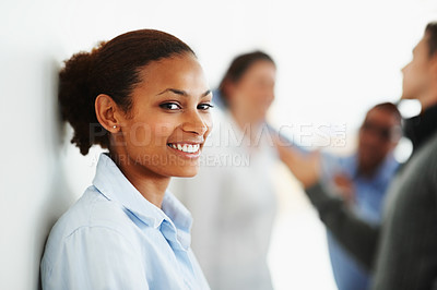 Buy stock photo Smiling African American business woman against a wall with colleagues at the back