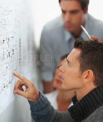 Buy stock photo Side view of a young business man with his colleagues studying a chart put up on the wall