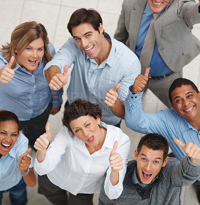 Buy stock photo Top view of a happy team of business colleagues gesturing a thumbs up sign