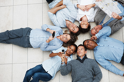 Buy stock photo Business leisure - Colleagues lying in circle doing various activities
