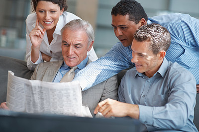 Buy stock photo Business people reading the financial newspaper at office