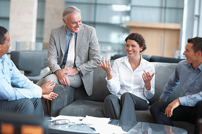 Buy stock photo Smiling team of business colleagues sitting relaxed the office lounge and having a casual chat