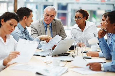 Buy stock photo Multi ethnic business executives sitting round a table discussing a business proposal