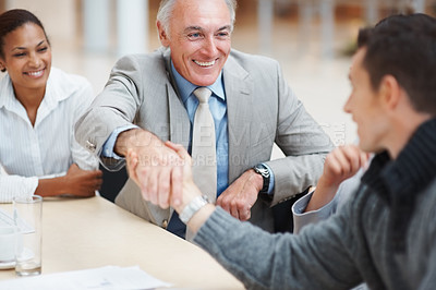 Buy stock photo Successful business partners handshaking after deal at a meeting