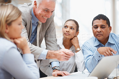 Buy stock photo Senior business manager discussing a new project on laptop with colleagues