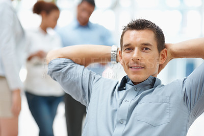 Buy stock photo Successful young business man relaxing with colleagues in the background