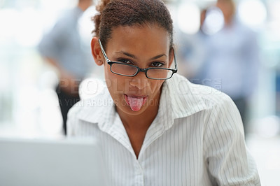 Buy stock photo Mischievous African American business woman showing you her tongue while at the office