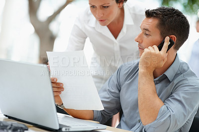 Buy stock photo Business man handing a document to a colleague while speaking over the mobile phone