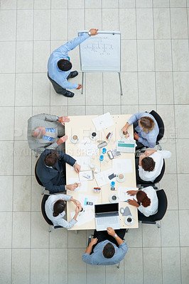 Buy stock photo Top view of a colleagues working out business plans at a meeting
