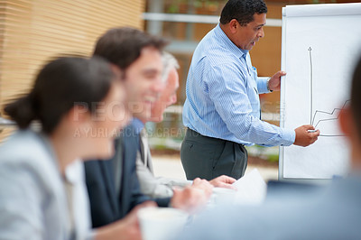 Buy stock photo Mixed race business man working out his presentation during a meeting