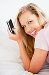 Happy cute female using her new cell phone while lying on bed