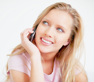 Buy stock photo Young beautiful woman using a cell phone while looking up against white