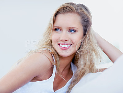 Buy stock photo Relaxed and smiling young woman on a couch and looking away