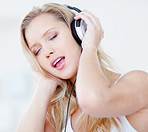 Cute woman enjoying to music over headphones