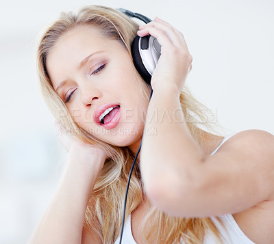 Buy stock photo Blond female enjoying her favorite song over the headphones
