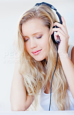 Buy stock photo Happy young woman enjoying pleasant music over the headphones