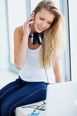 Buy stock photo Happy female taking a break from listening to music and talking on the cellphone