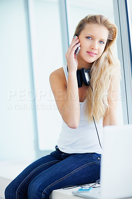 Buy stock photo Pretty woman taking a break from listening to music and speaking on the cellphone