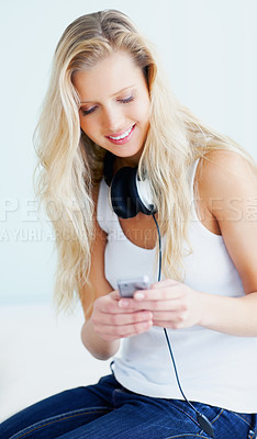 Buy stock photo Beautiful young woman with headphones selecting a song on her MP3 player