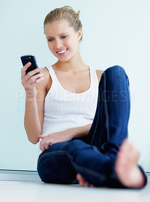 Buy stock photo Pretty happy woman sitting against a wall and reading a text message