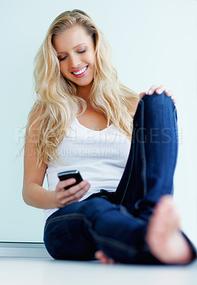 Buy stock photo Cute smiling female reading a text message while sitting on the floor