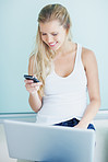Happy woman with laptop and reading text message on cellphone