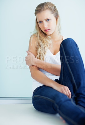Buy stock photo Young pretty female sitting against a wall in thought