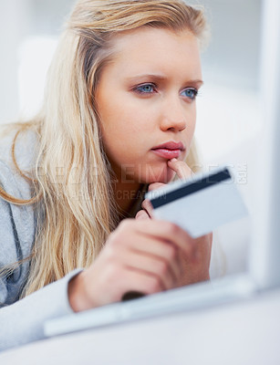 Buy stock photo Pretty thoughtful female using a laptop and a credit card