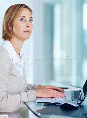 Buy stock photo Portrait of  middle aged woman looking away while working on laptop