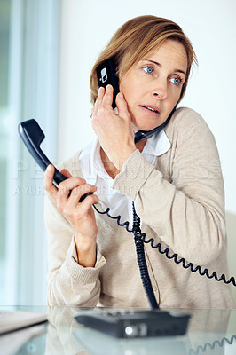 Buy stock photo Portrait of mature businesswoman multitasking by tackling telephone calls working in office