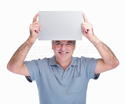 Buy stock photo Portrait of a happy senior man holding a blank billboard over head against white