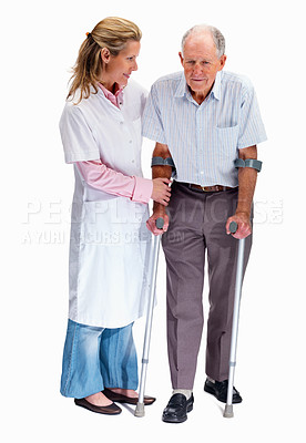 Buy stock photo Full length portrait of a physical therapist helps a man on crutches against white background