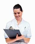 Pretty nurse smiling writing on a pad against white