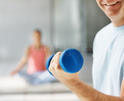 Buy stock photo Mid section of a man working out with a dumbbell at the gym