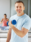Happy man using a dumbbell while at the gym
