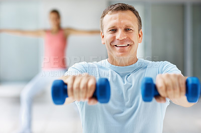 Buy stock photo Handsome middle aged man working out with dumbbells while at the gym