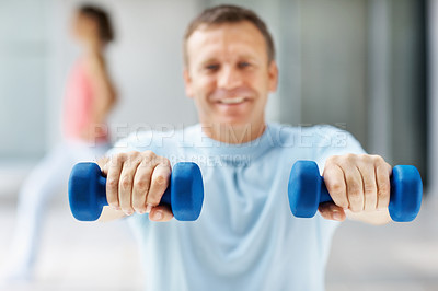 Buy stock photo Smiling middle aged man working out with dumbbells while at the gym