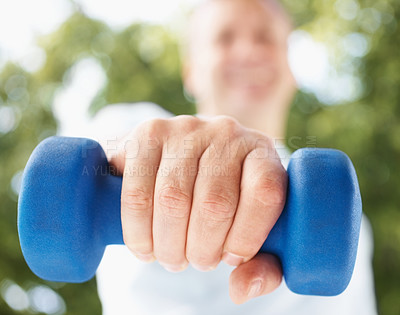 Buy stock photo Closeup of a fit guy exercising with a dumbbell while outdoors , focus on his hand