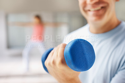 Buy stock photo Closeup of a blue dumbbell being held by a man while he works out at the gym