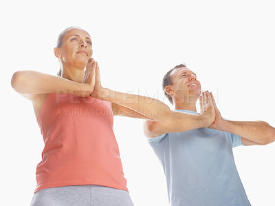 Buy stock photo Upward view of a couple practicing yoga together against white with hands joined