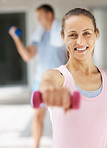 Happy mature female using a dumbbell at the gym
