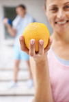 Woman holding a fresh orange while at the gym