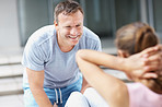 Smiling male trainer working out with a female at the gym